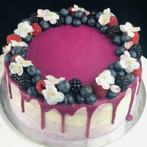 Top of Lemon and Blueberry celebration cake with fruit and flower decoration.