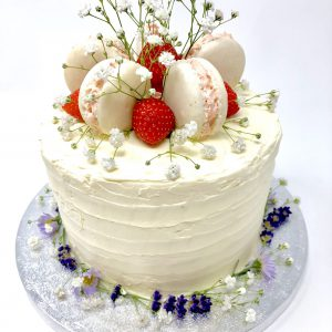Handcrafted luxury celebration cake with fresh strawberries and freshly baked French macarons on top