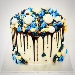 Bespoke gourmet celebration cake with blue and gold ganache drip and handmade macarons and meringues