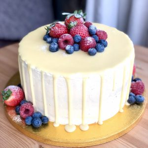 Elegant, freshly baked strawberry and vanilla sponge cake coated in a white ganache drip and berries