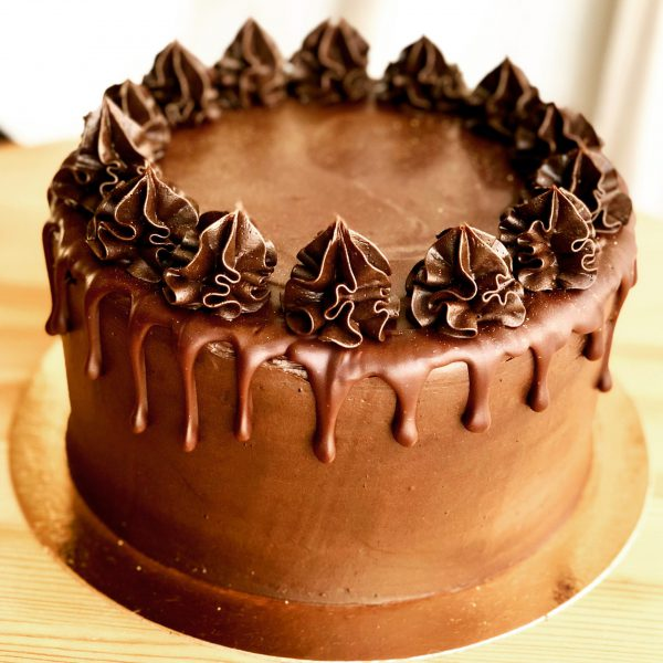 Indulgent handmade dark chocolate cake with chocolate icing and drip ganache topping