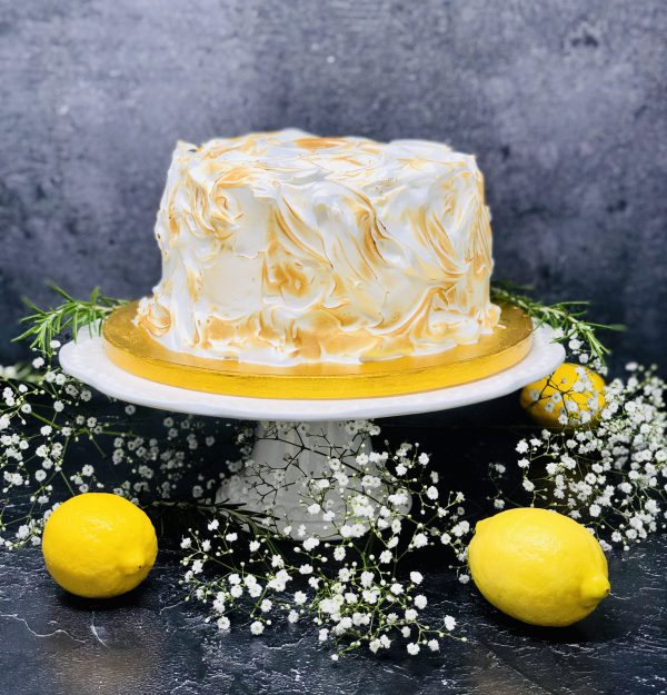 Luxurious lemon meringue cake covered in Italian meringue