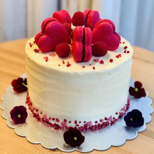 Handcrafted raspberry and vanilla sponge cake topped with pink macarons