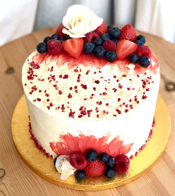 Elegant strawberry and vanilla celebration cake with fresh flowers and berries