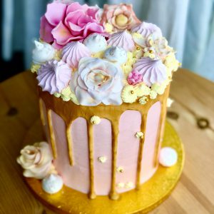 Showstopping handcrafted pink and gold birthday cake with pink meringues and gold ganache drip
