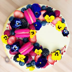 Yellow flower, pink French macaron and berry decoration on handcrafted berry cake